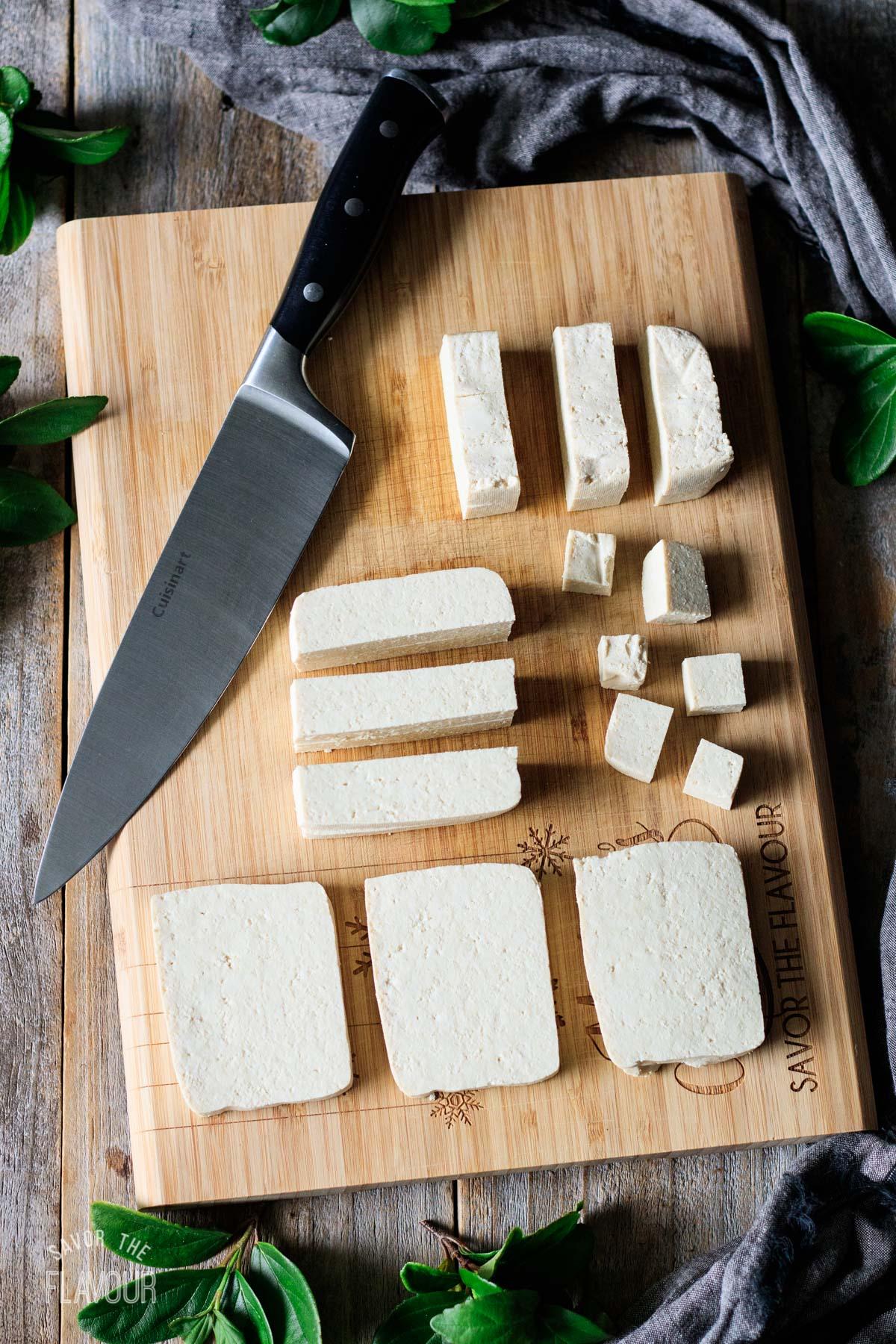 cutting the tofu into cubes on a bamboo cutting board