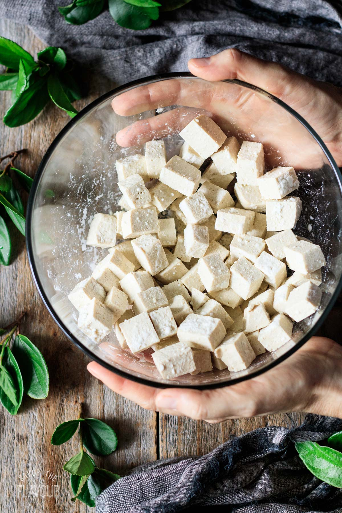 person tossing the tofu cubes with cornstarch