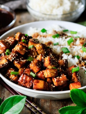 white bowl of teriyaki tofu with white rice and chopsticks