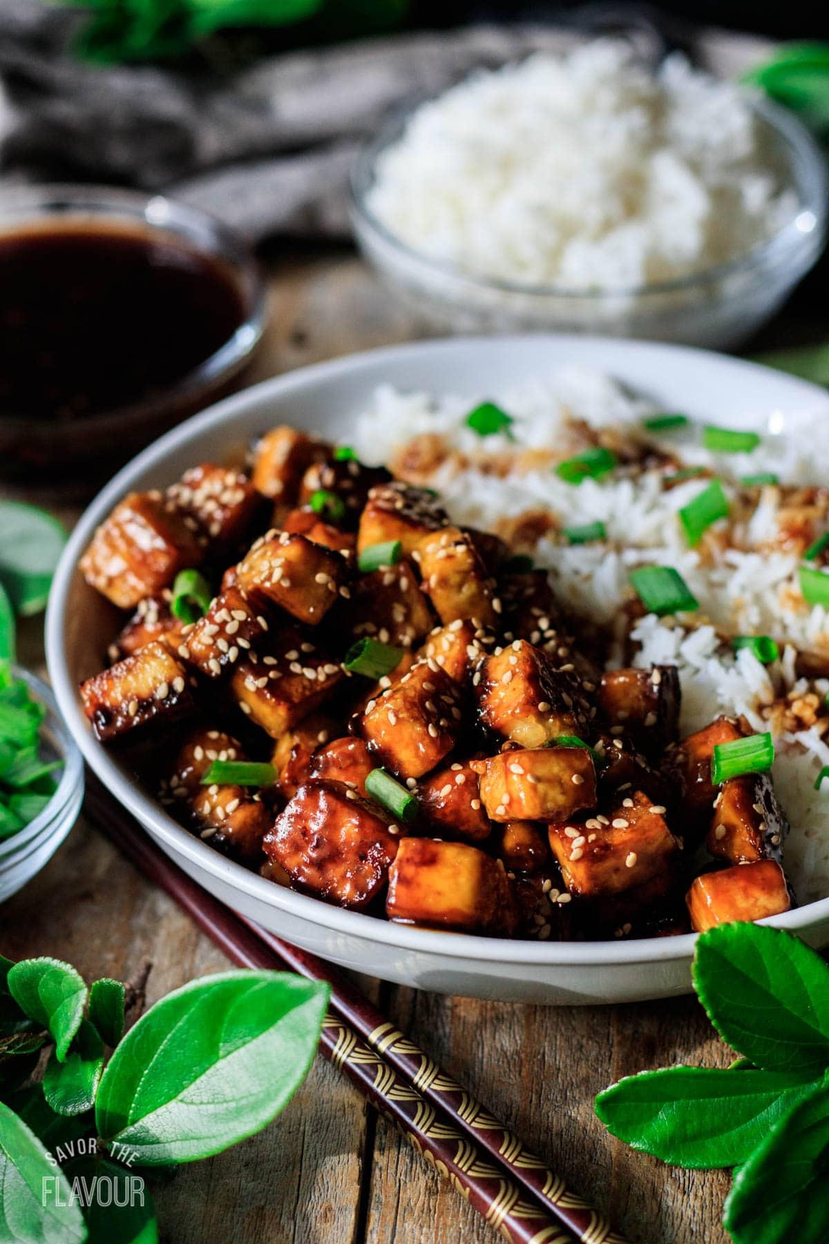 bowl of teriyaki tofu with rice and chopsticks