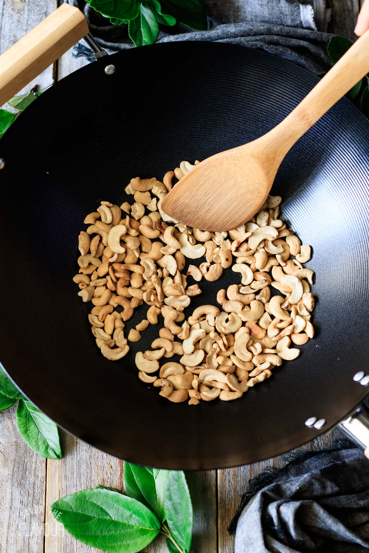 stirring toasted cashews in a wok