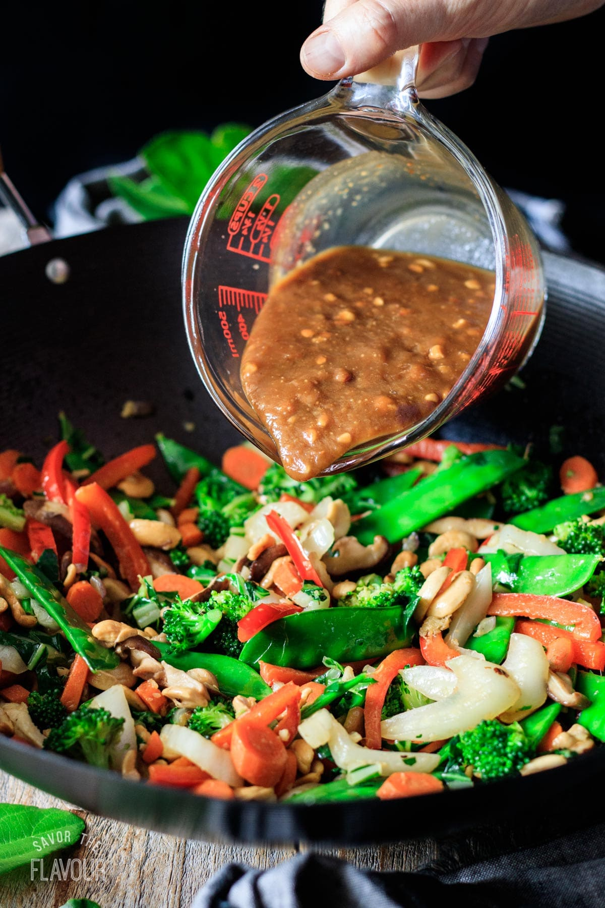 pouring the peanut sauce into the stir fry