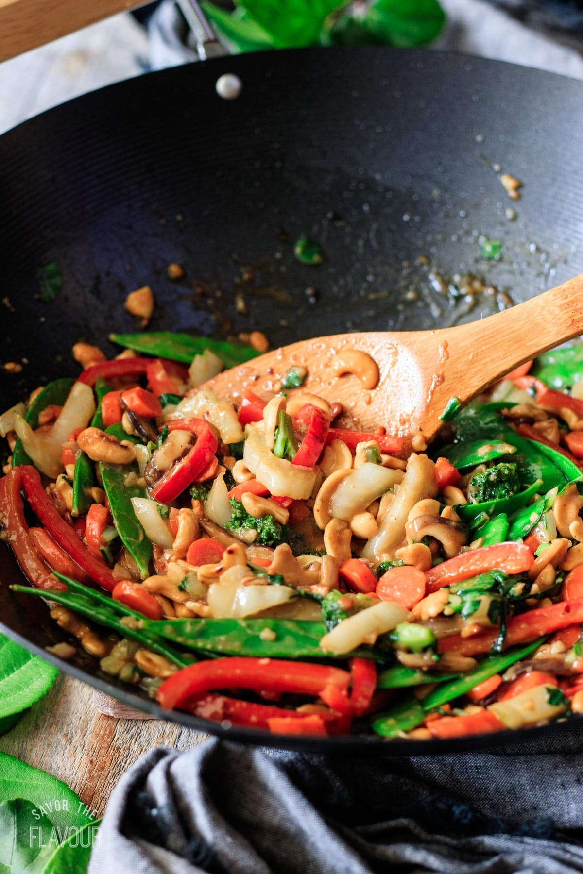 mixing the stir fry vegetables with the peanut sauce