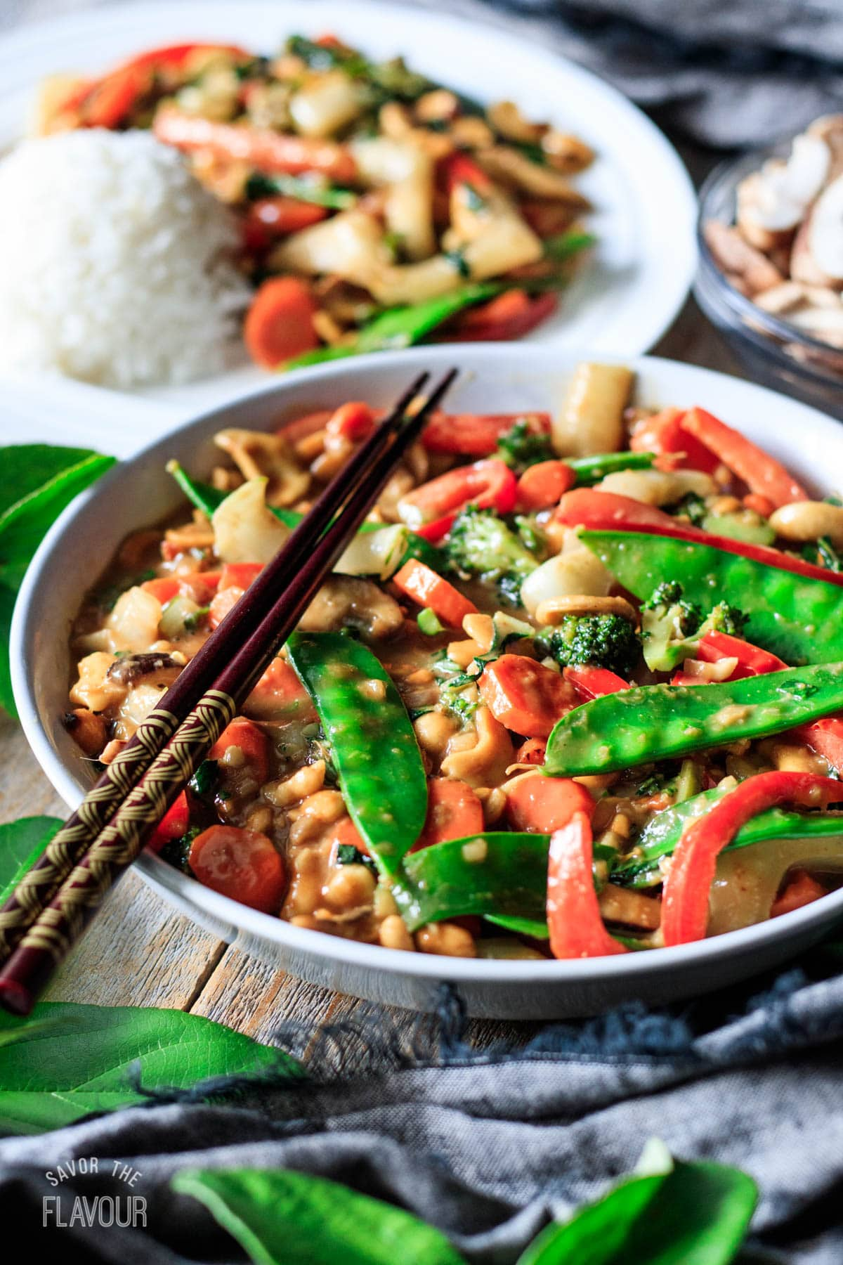 white bowl of Thai vegetable stir fry with chopsticks