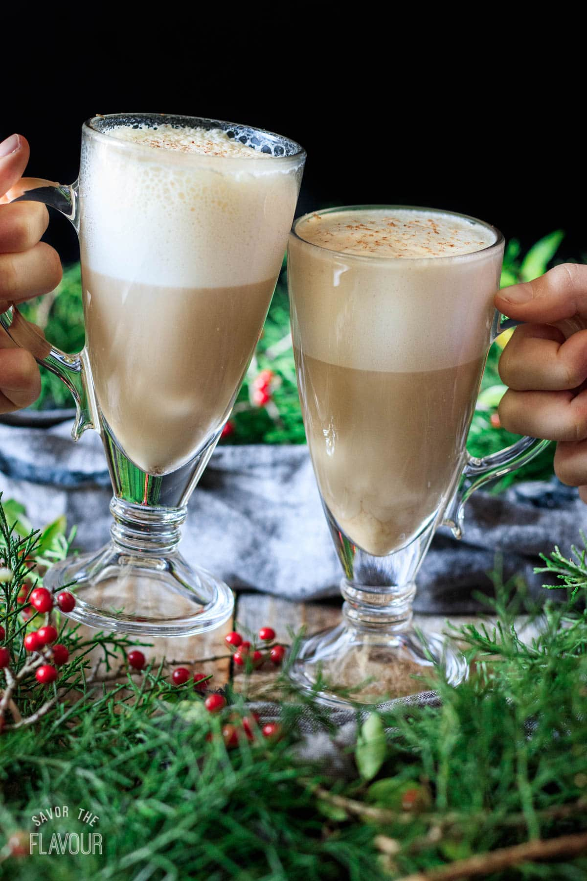 people doing a toast with two eggnog lattes