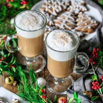 two gingerbread lattes with a plate of gingerbread cookies