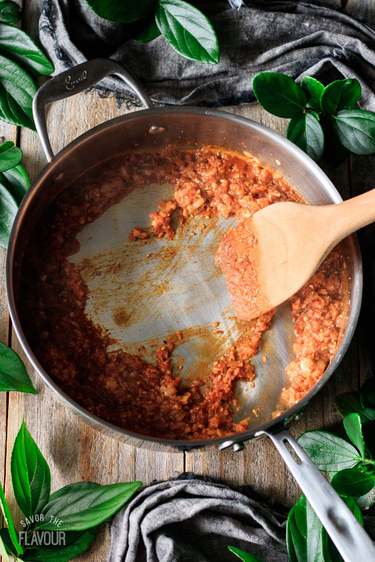 person stirring the vegetable and spice mixture in a skillet