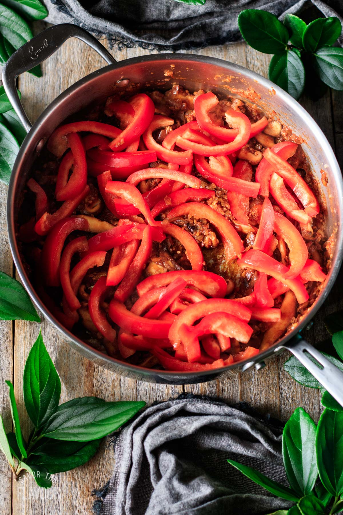 sliced red peppers and other veggies in a skillet