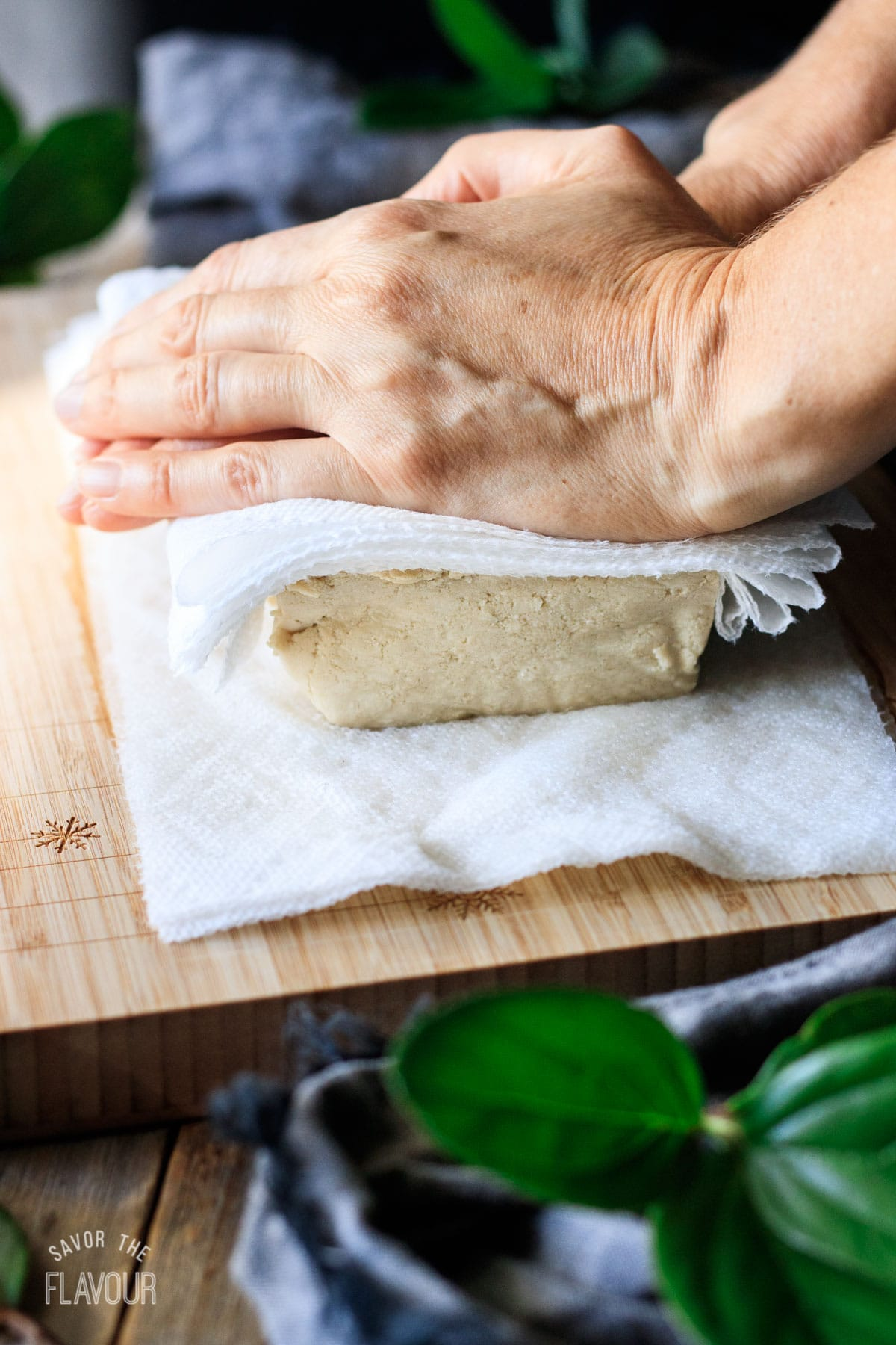 person pressing tofu with paper towels