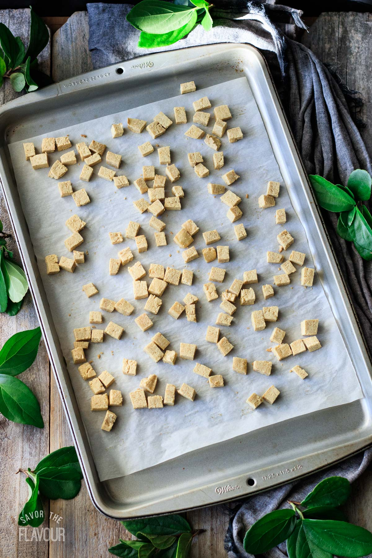 cubes of tofu on a parchment-lined cookie sheet