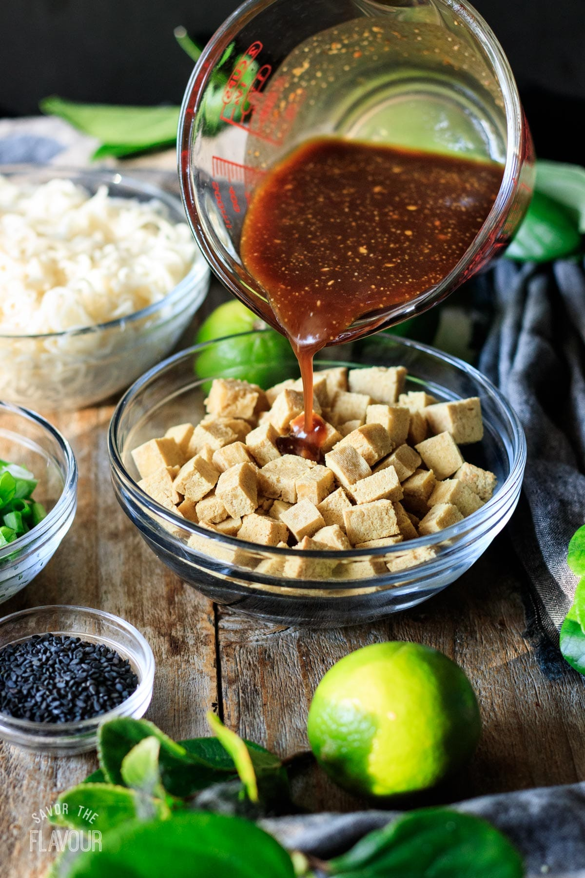 pouring peanut sauce on cubes of baked tofu
