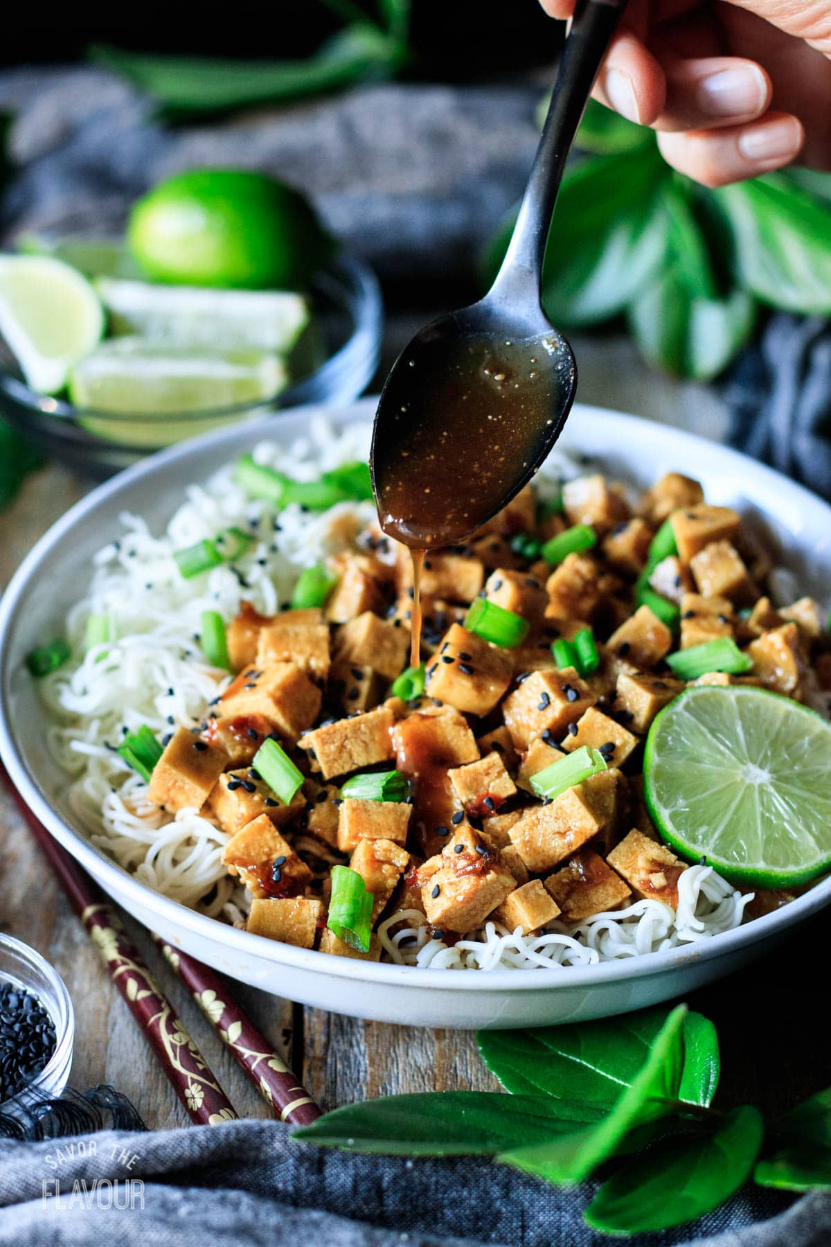 person drizzling peanut sauce on crispy baked tofu bowl