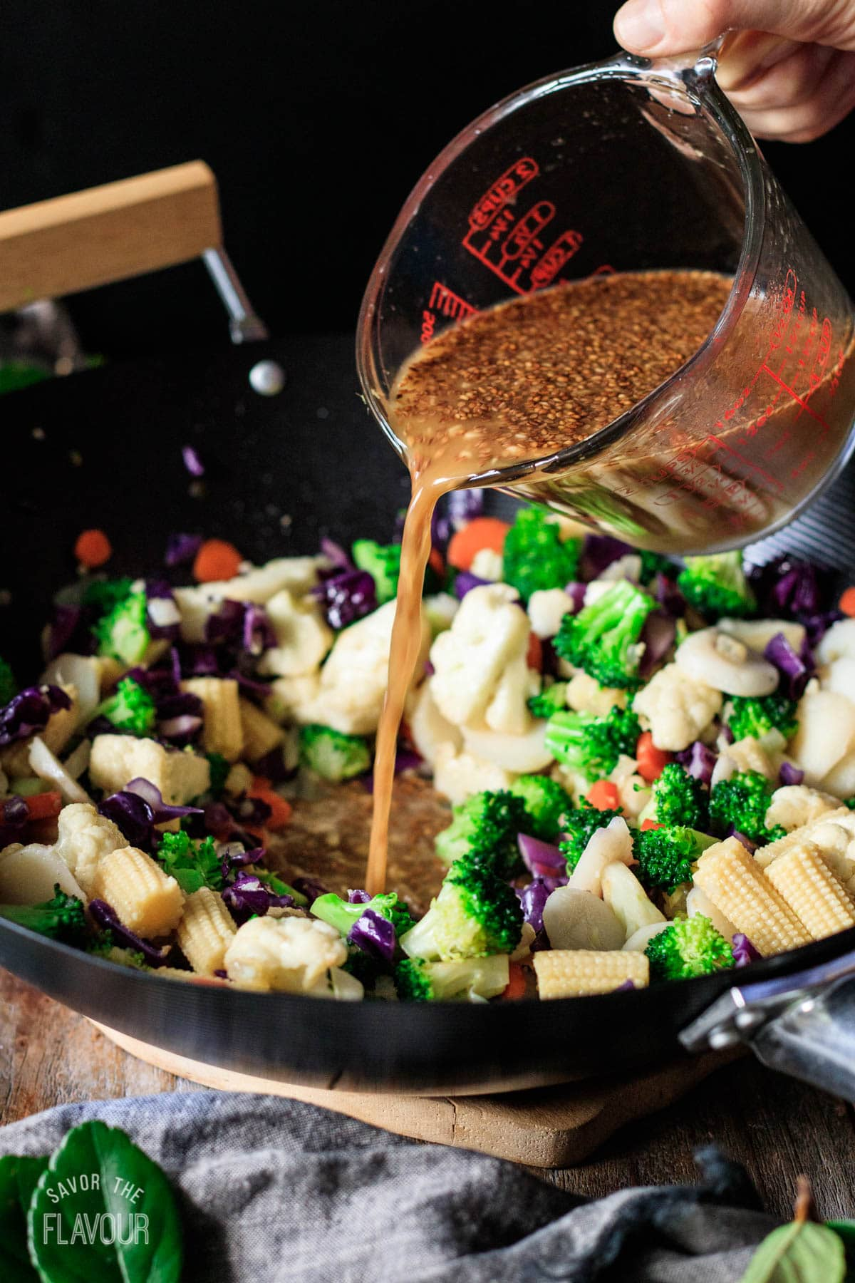 person pouring vegan stir fry sauce into a wok of cooked veggies
