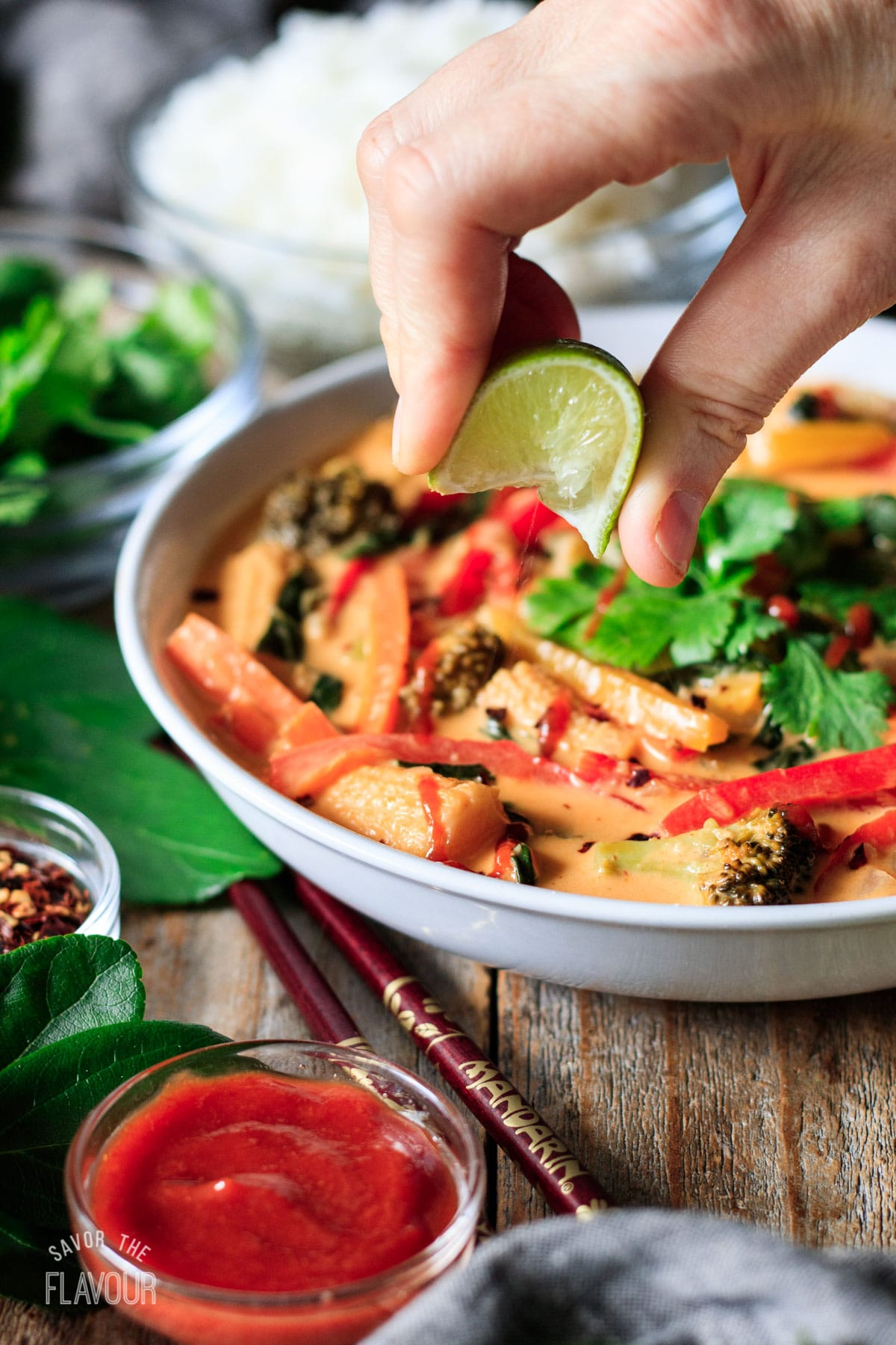 person squeezing lime juice on a bowl of Thai red curry