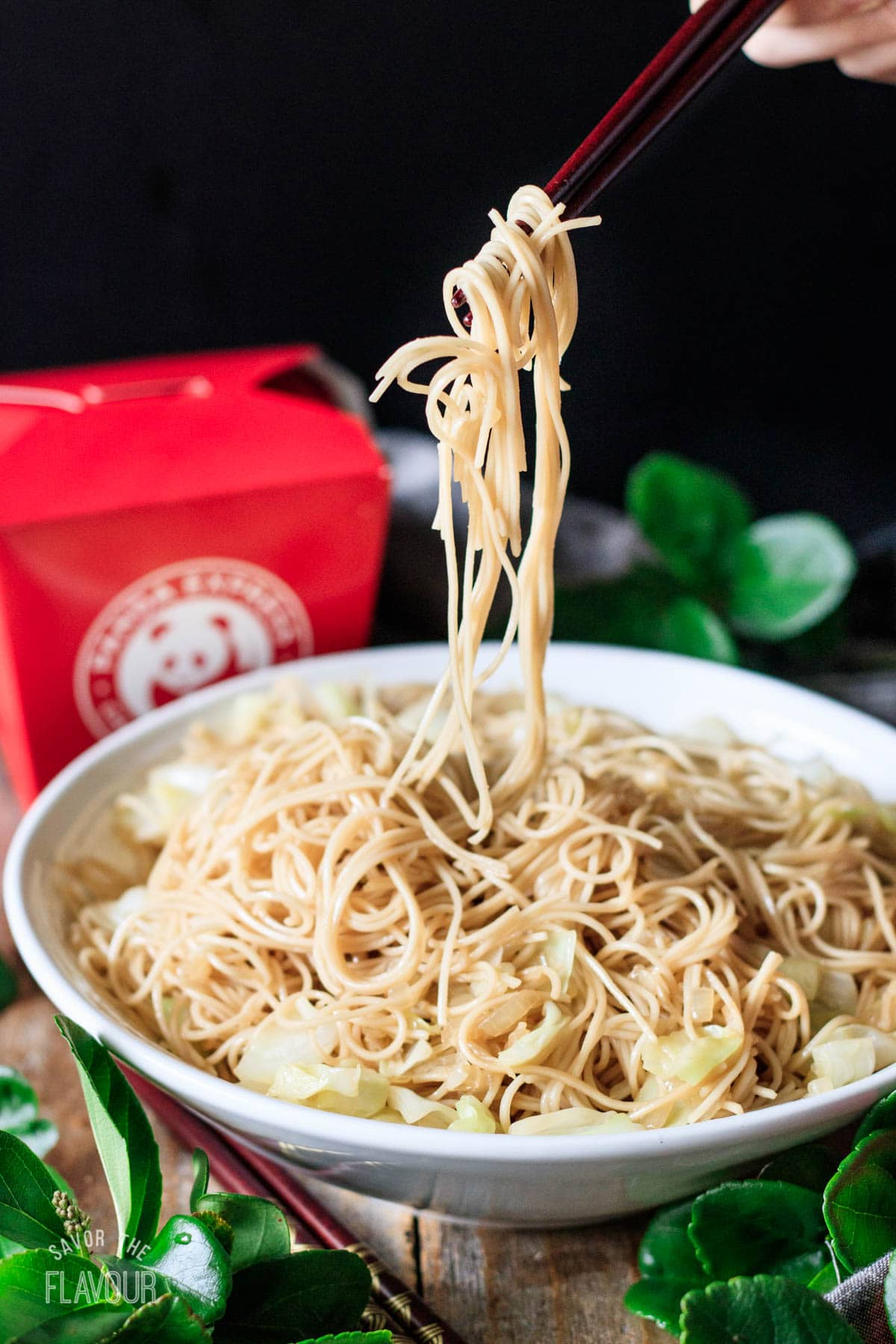 person holding up chow mein noodles with chopsticks