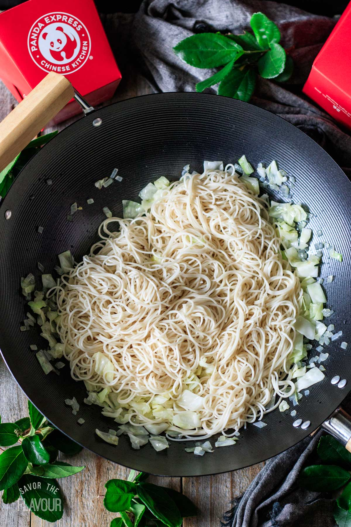 cooked mein noodles and sauteed veggies in a wok