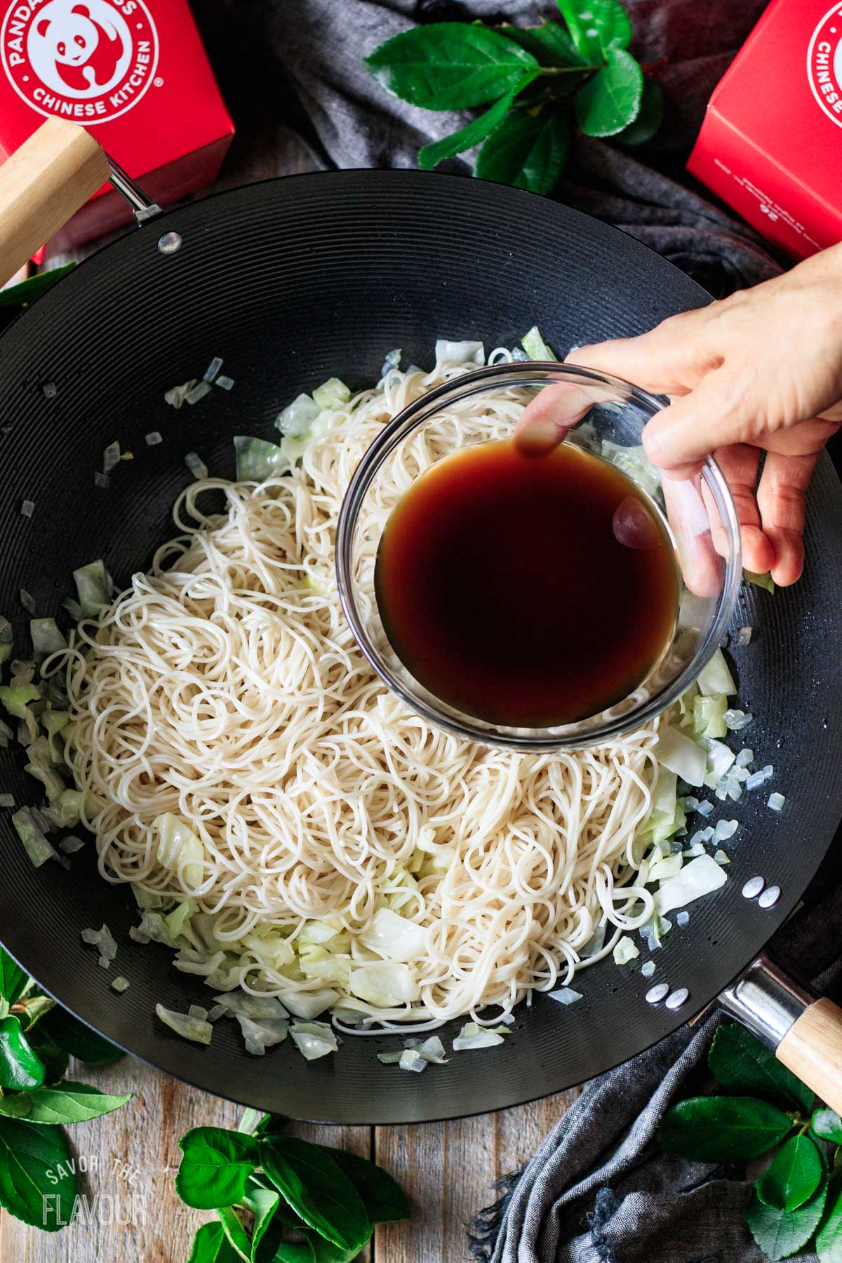 pouring the sauce on the cooked noodles and veggies