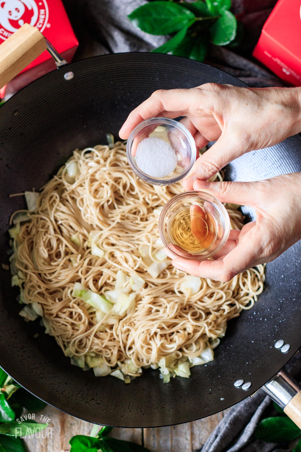 person adding sesame oil and salt to the chow mein