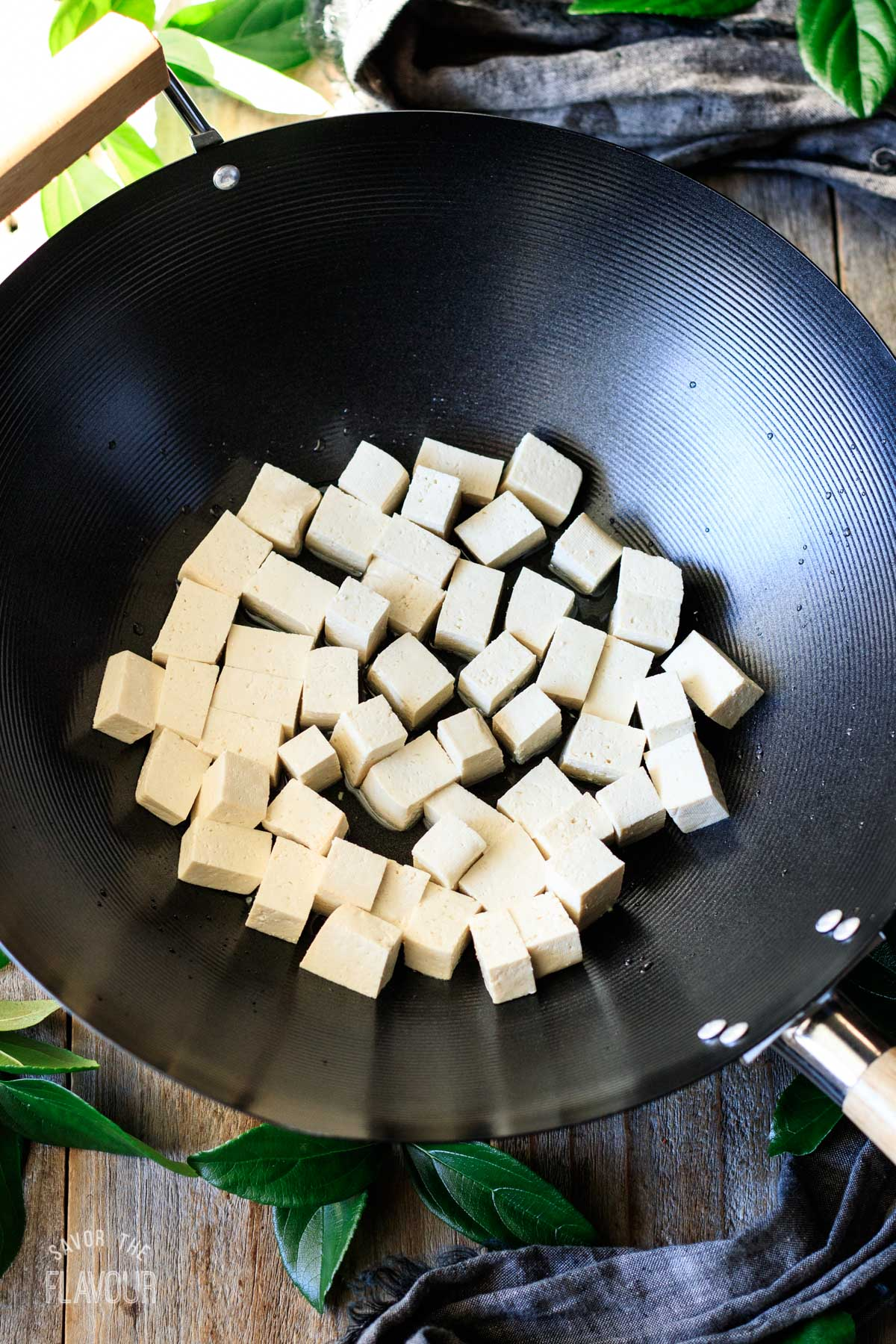 cubes of tofu frying in a large black wok