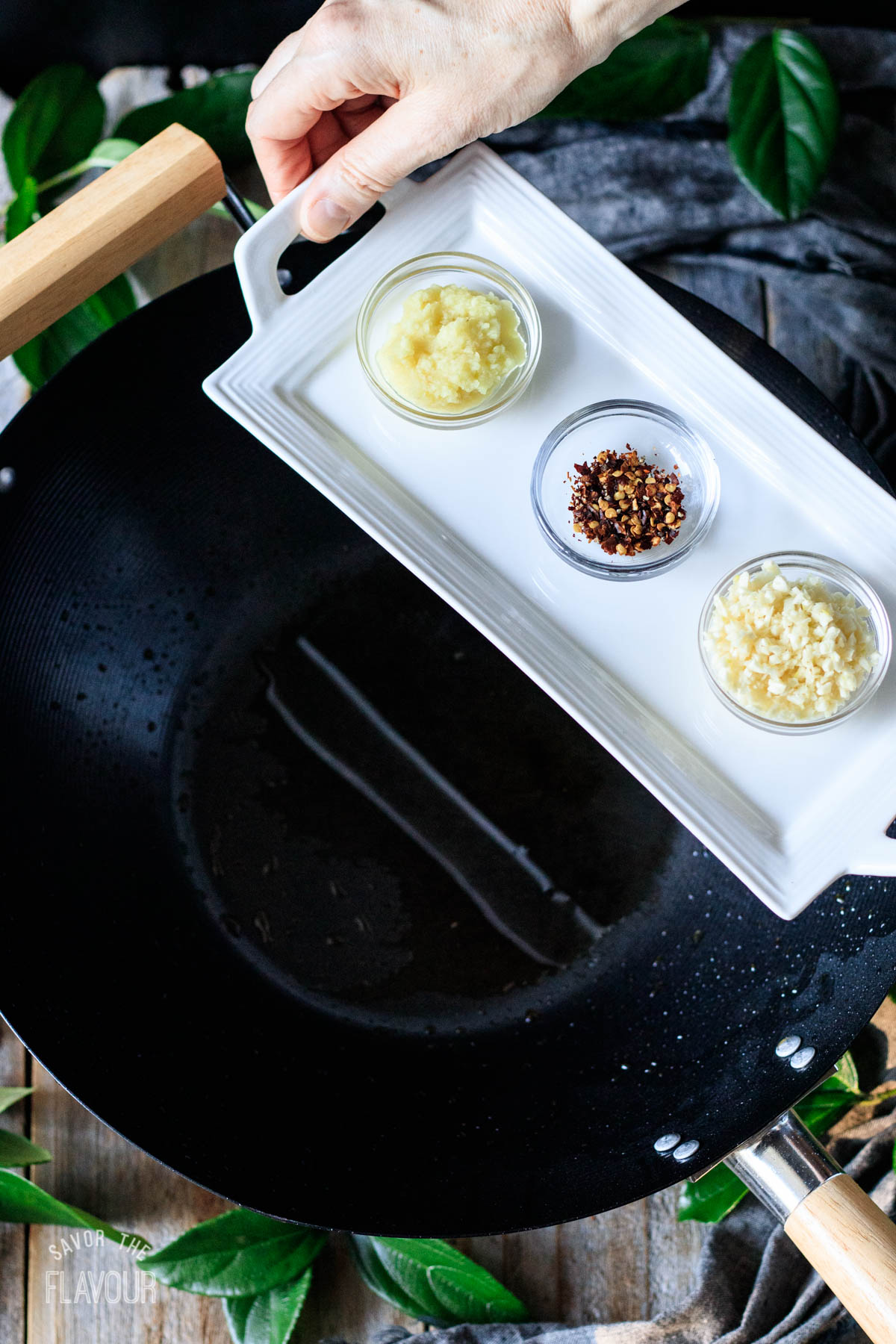 person holding a tray with small bowls of spices and aromatics