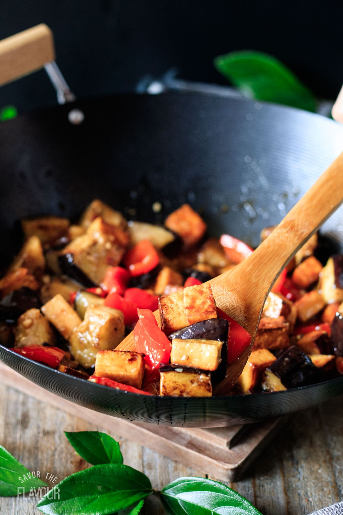 cooked eggplant tofu in a wok with a bamboo spoon