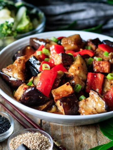bowl of Panda Express eggplant tofu with bowls of garnishes