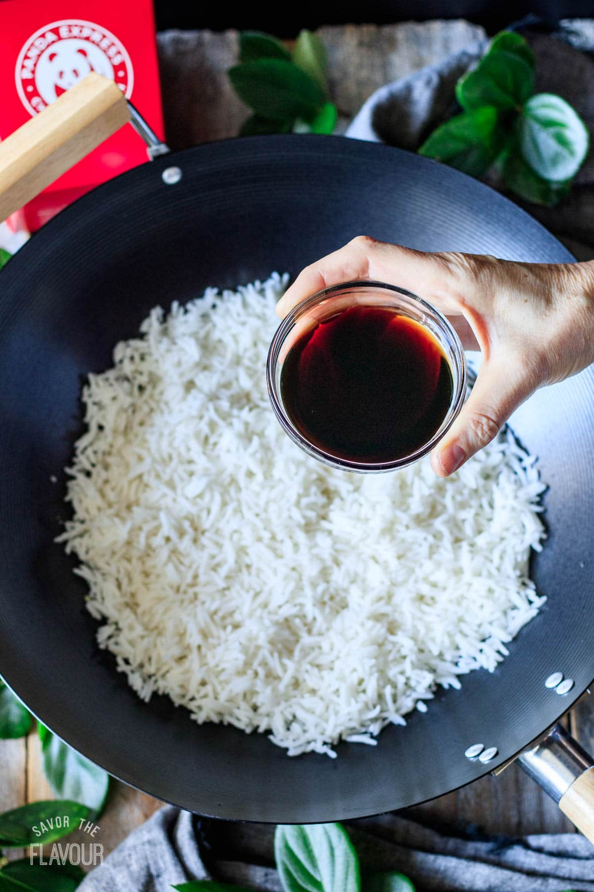 pouring liquid aminos on white rice in a wok