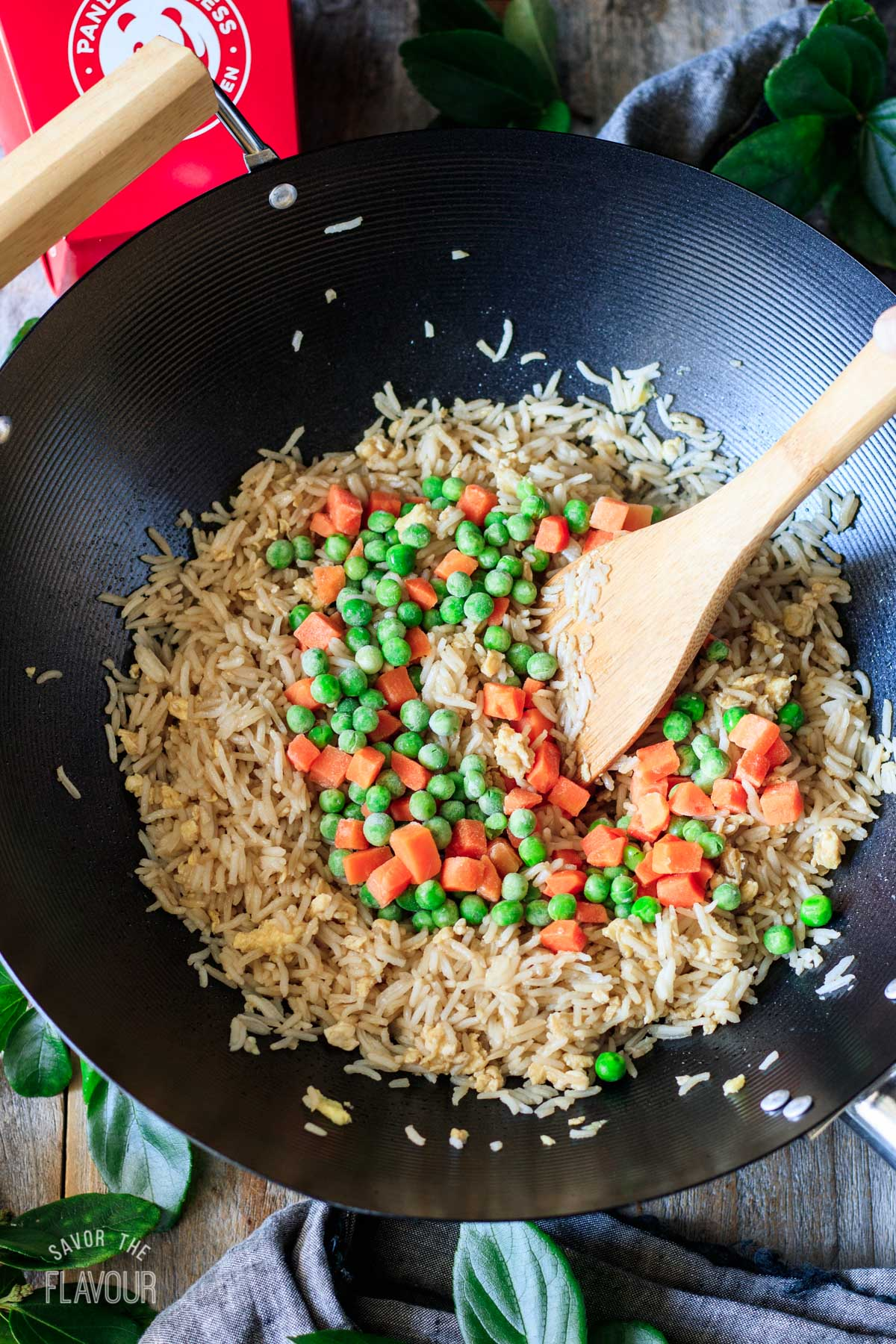stirring peas and carrots into the cooked rice mixture