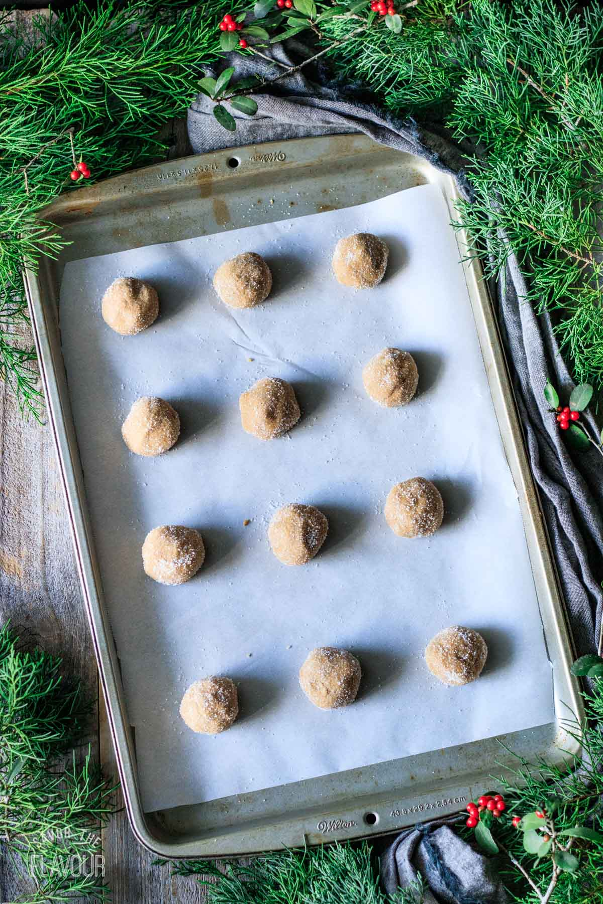 balls of vegan gingersnap cookie dough on a cookie sheet