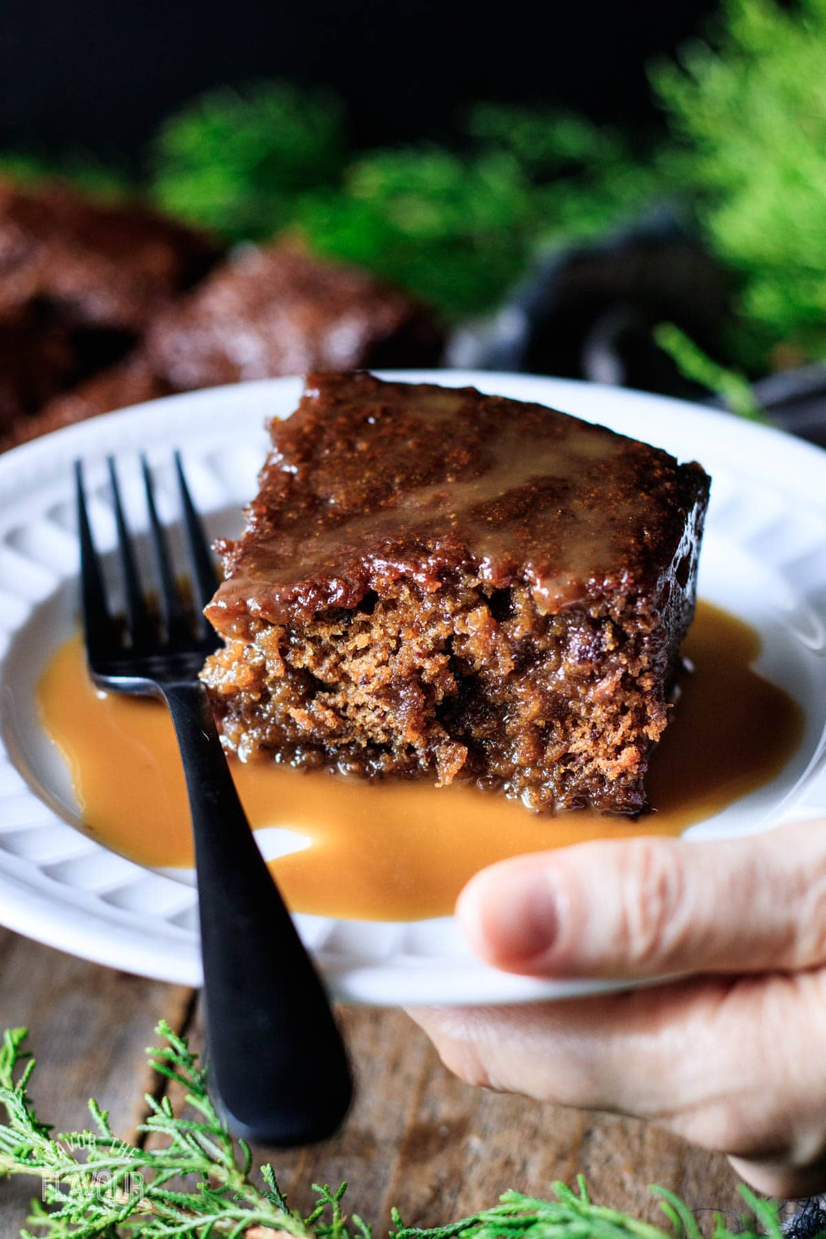 person holding a plate of vegan sticky toffee pudding with a fork