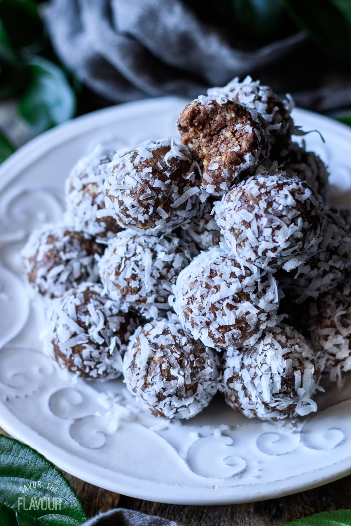 date protein balls stacked on a white plate