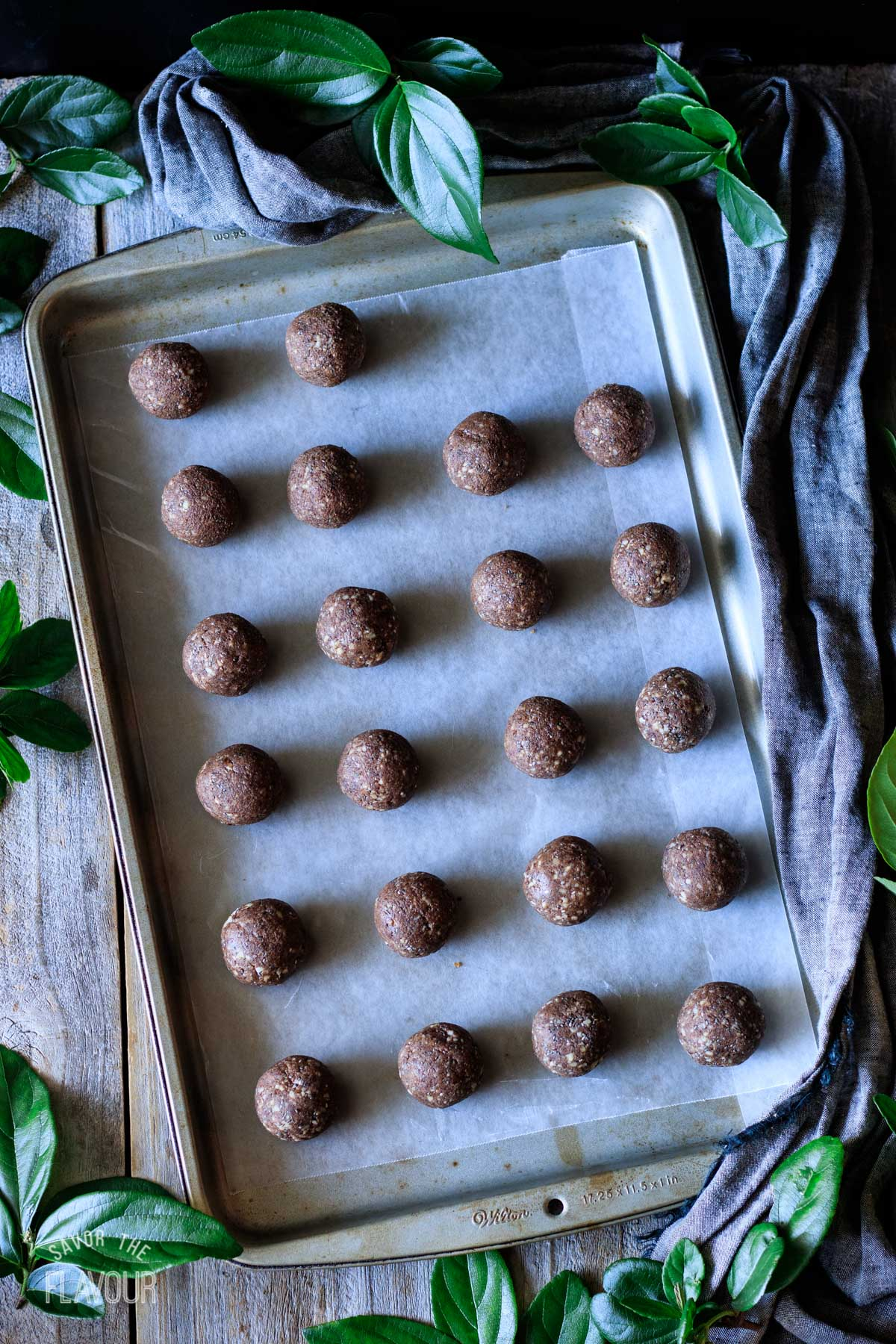 date protein balls spread apart on a cookie sheet
