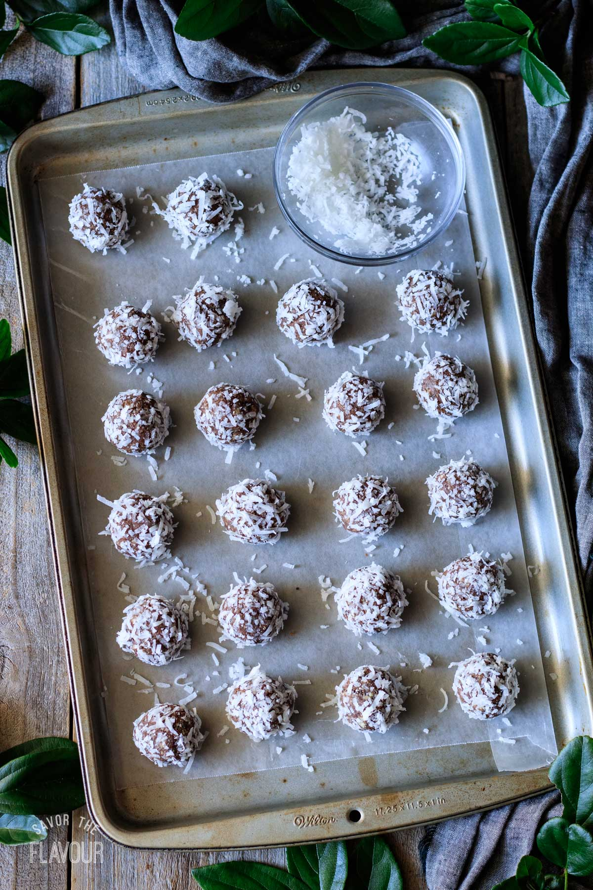 date protein balls rolled in coconut flakes and placed on a cookie sheet
