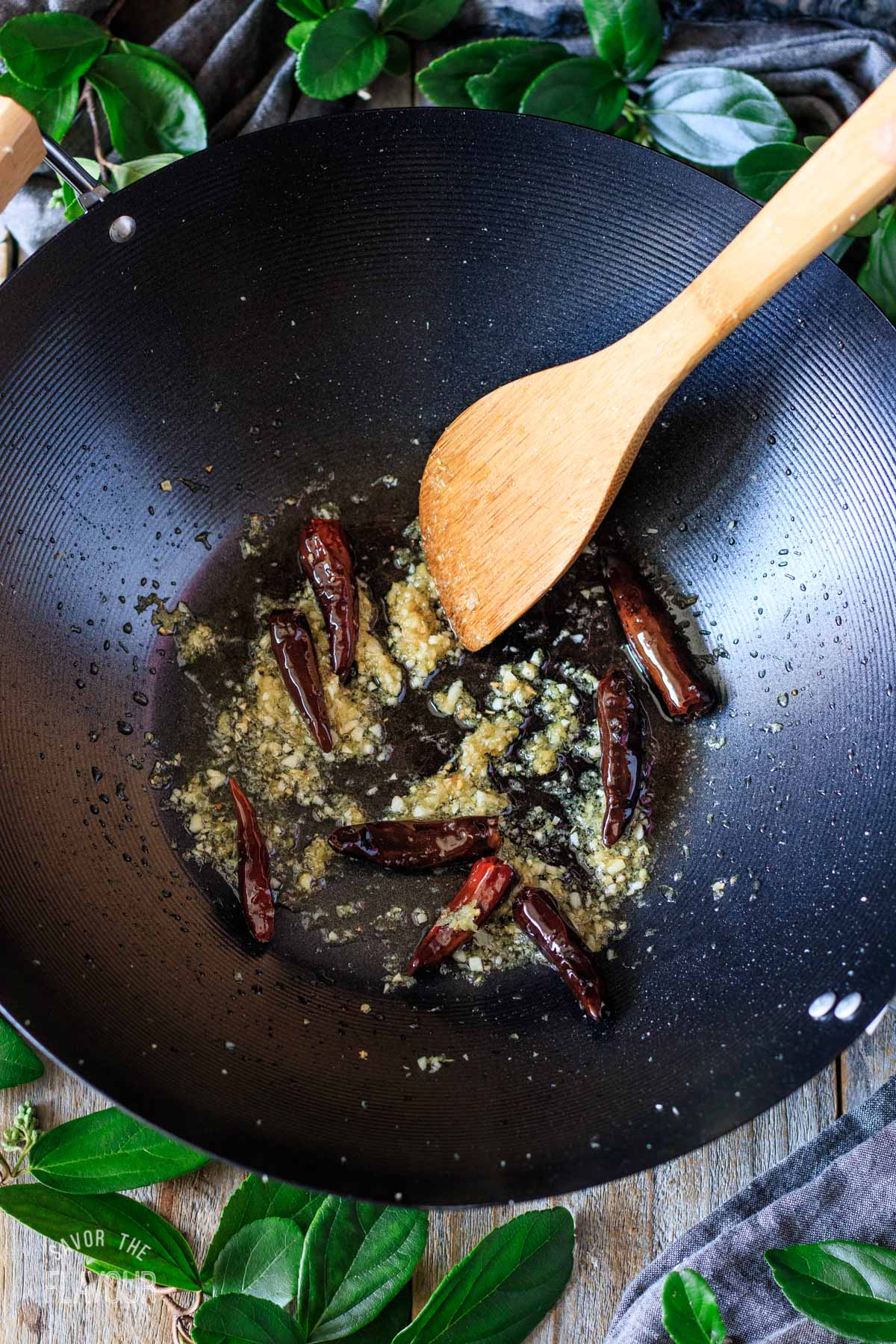 stir frying dried chiles and aromatics in a black wok