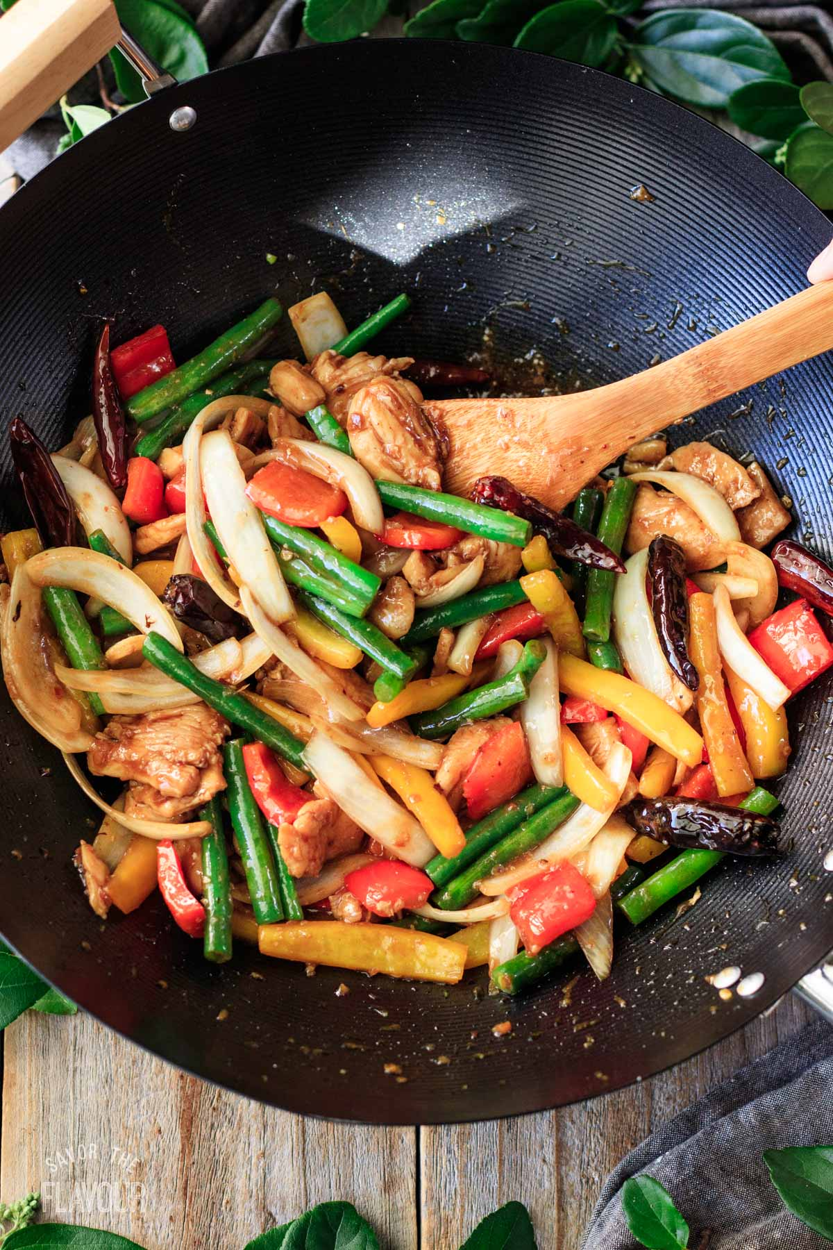person mixing the cooked chicken, veggies, and sauce together in a wok