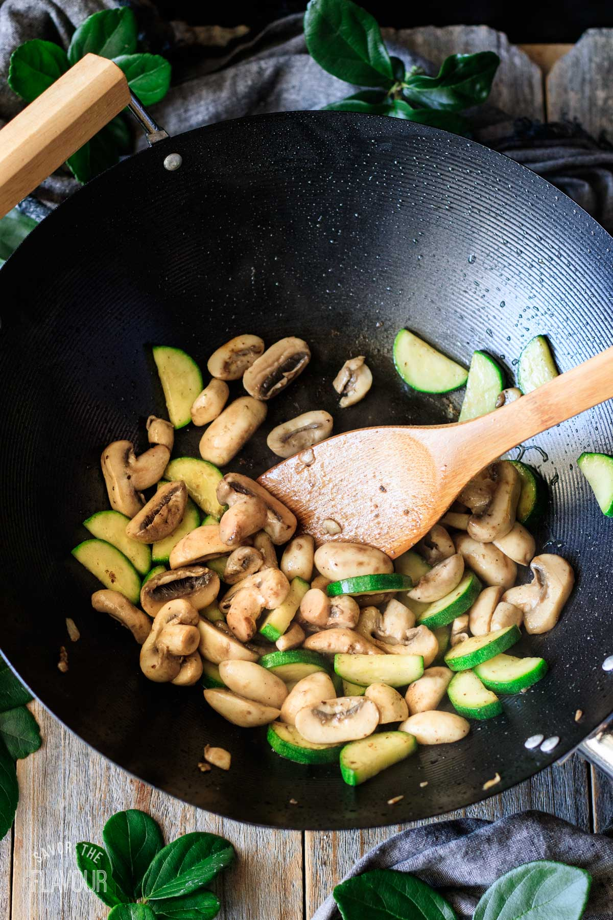 stir fried zucchini and mushrooms in a wok with a bamboo spoon