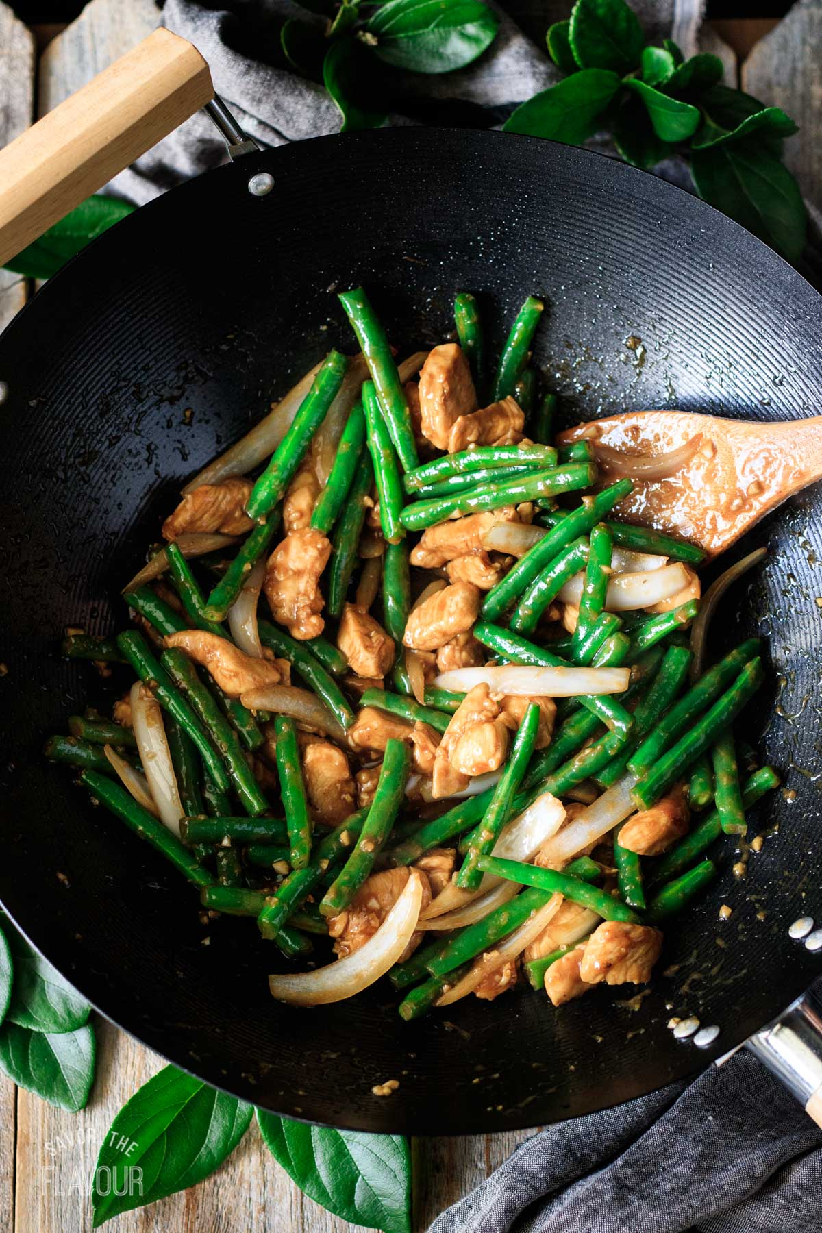 cooked string bean chicken in a wok with a bamboo spoon