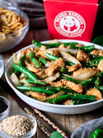 bowl of string bean chicken with two chopsticks and bowls of sides