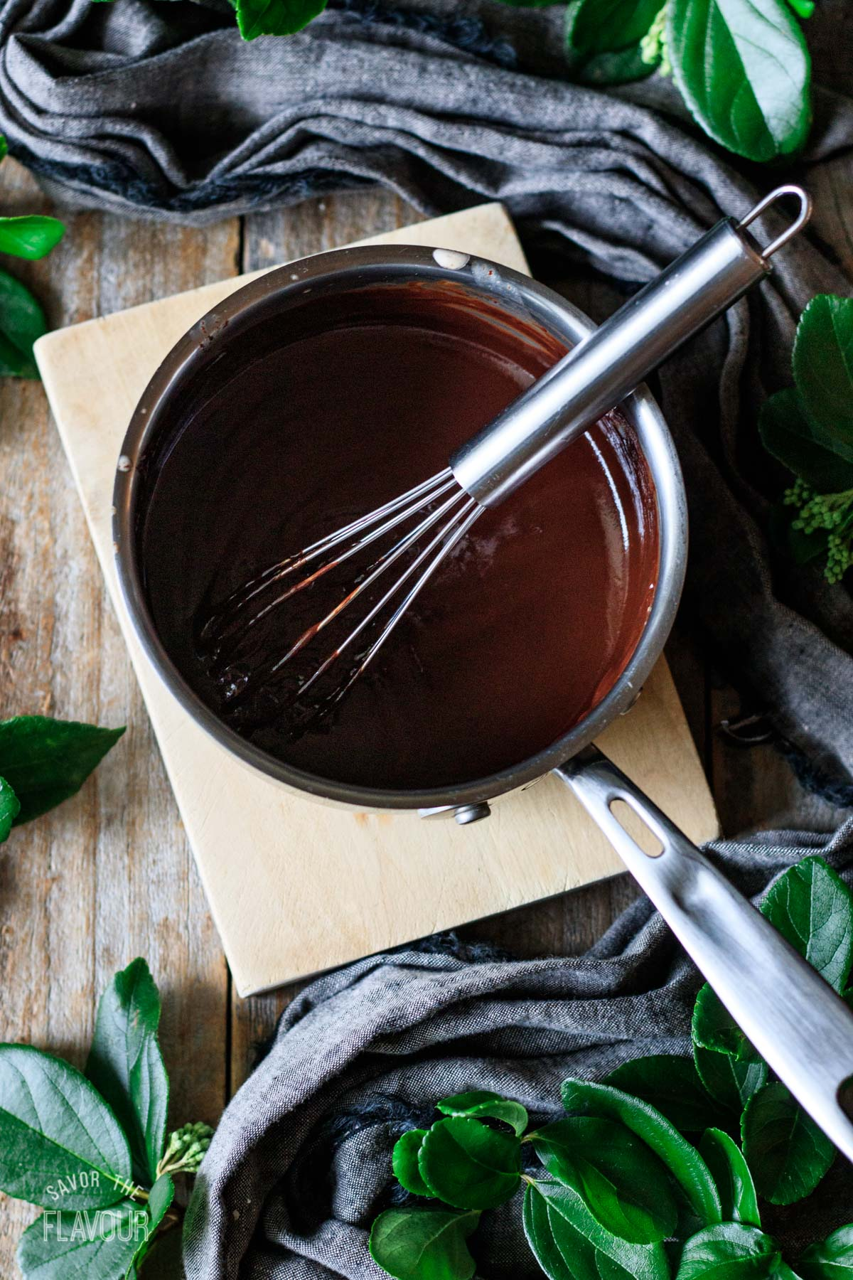 chocolate ganache in a small saucepan with a whisk