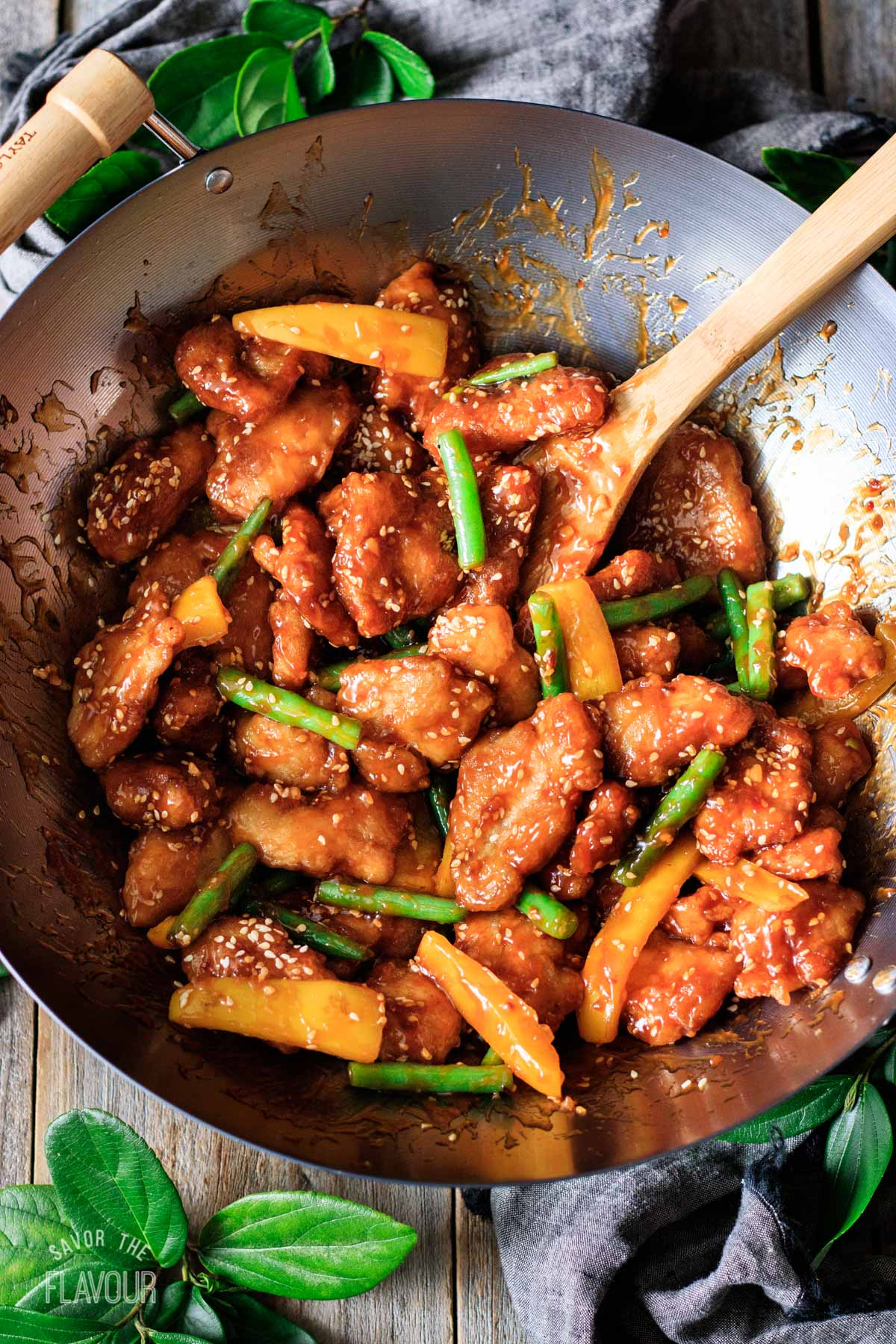 honey sesame chicken in a large wok with a bamboo spoon