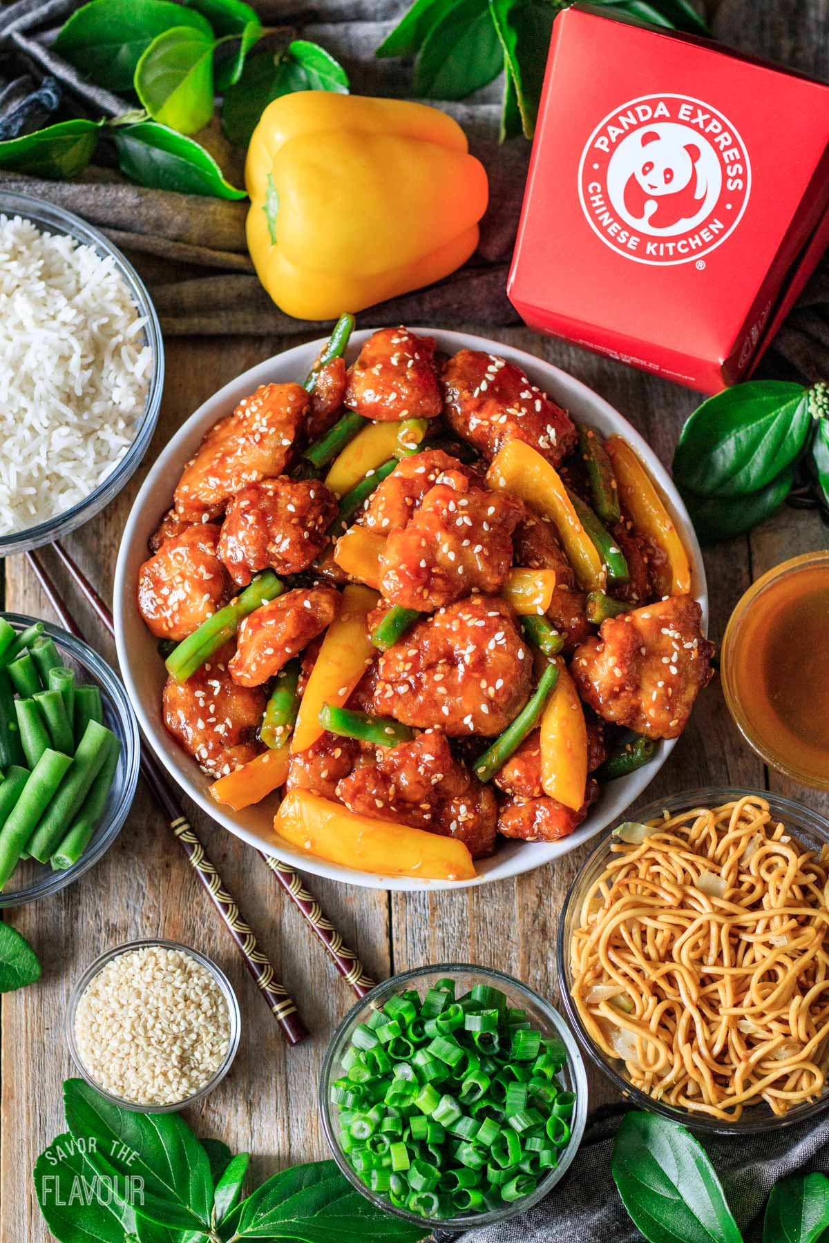 bowl of honey sesame chicken with bowls of sides and garnishes