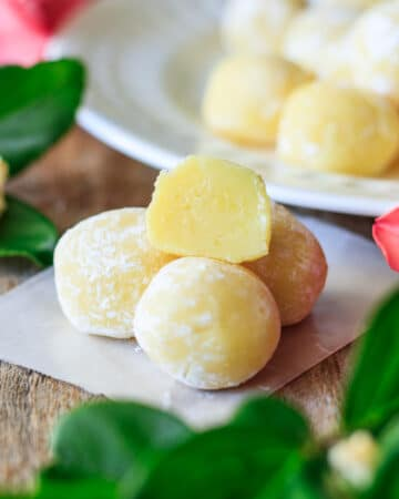 stack of four lemon truffles on a small piece of wax paper