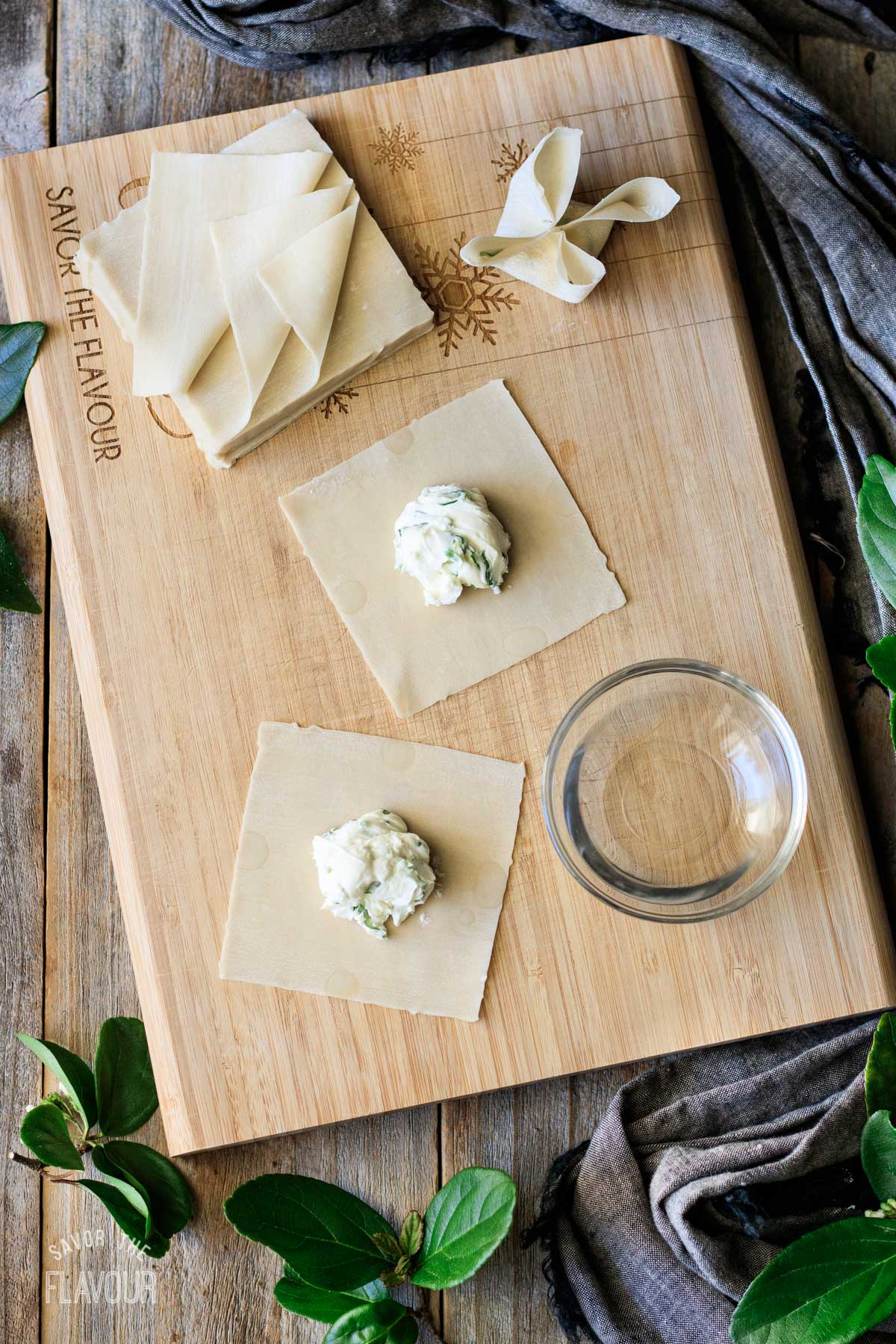 cream cheese filling and wontons on a cutting board