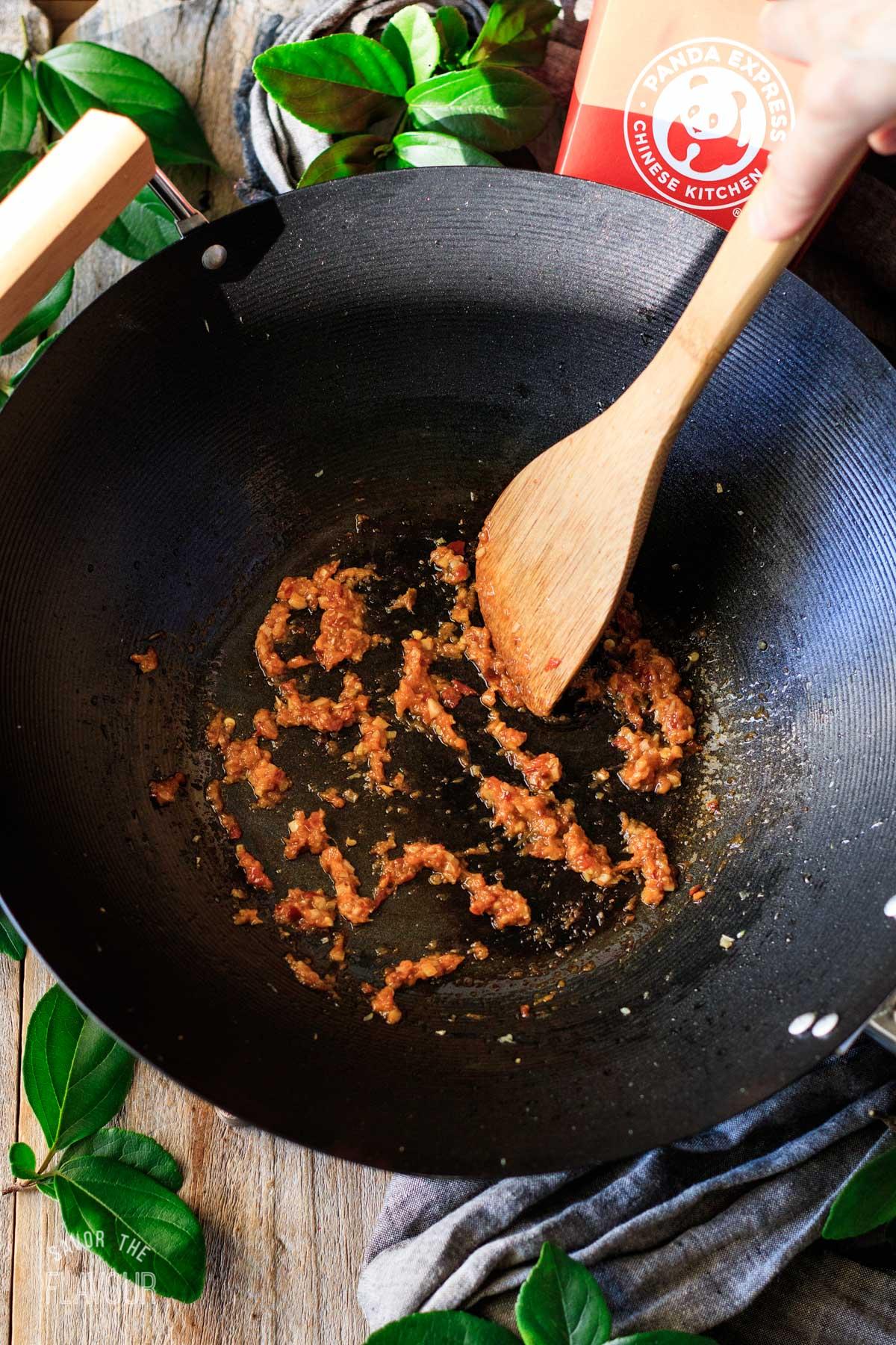 person cooking garlic, ginger, and sambal oelek in a wok