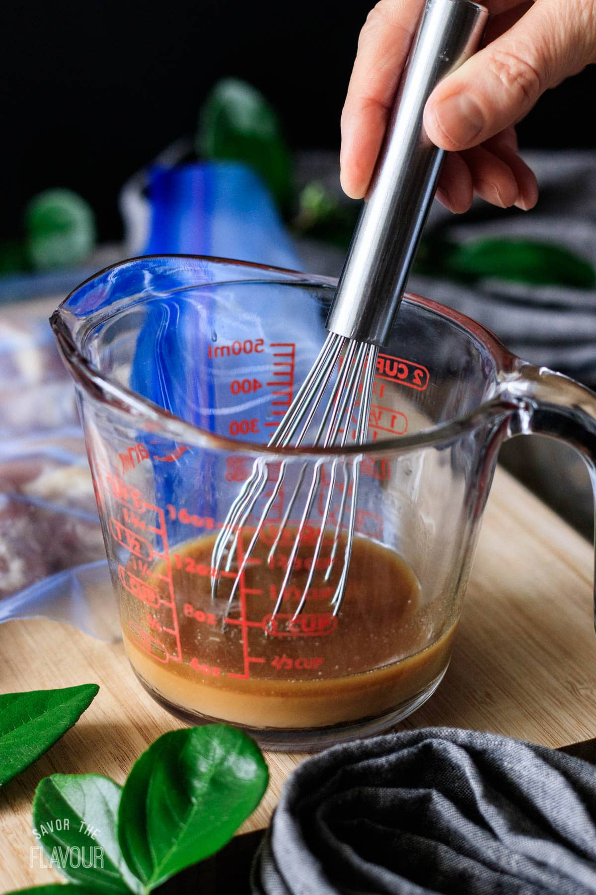 person whisking the chicken marinade in a glass container