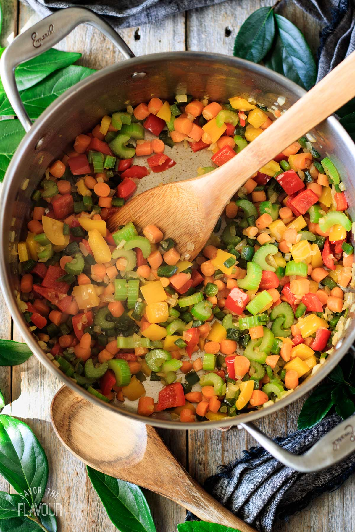 sauteed veggies in a large pot with a wooden spoon