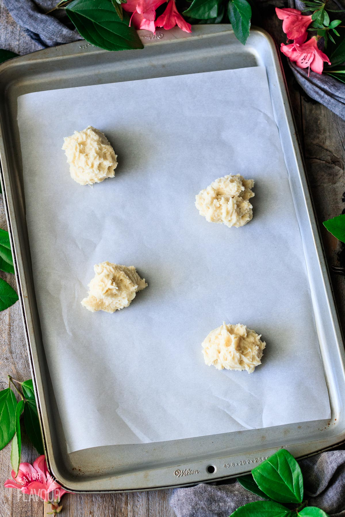 balls of unbaked lemon drop cookie dough on a cookie sheet