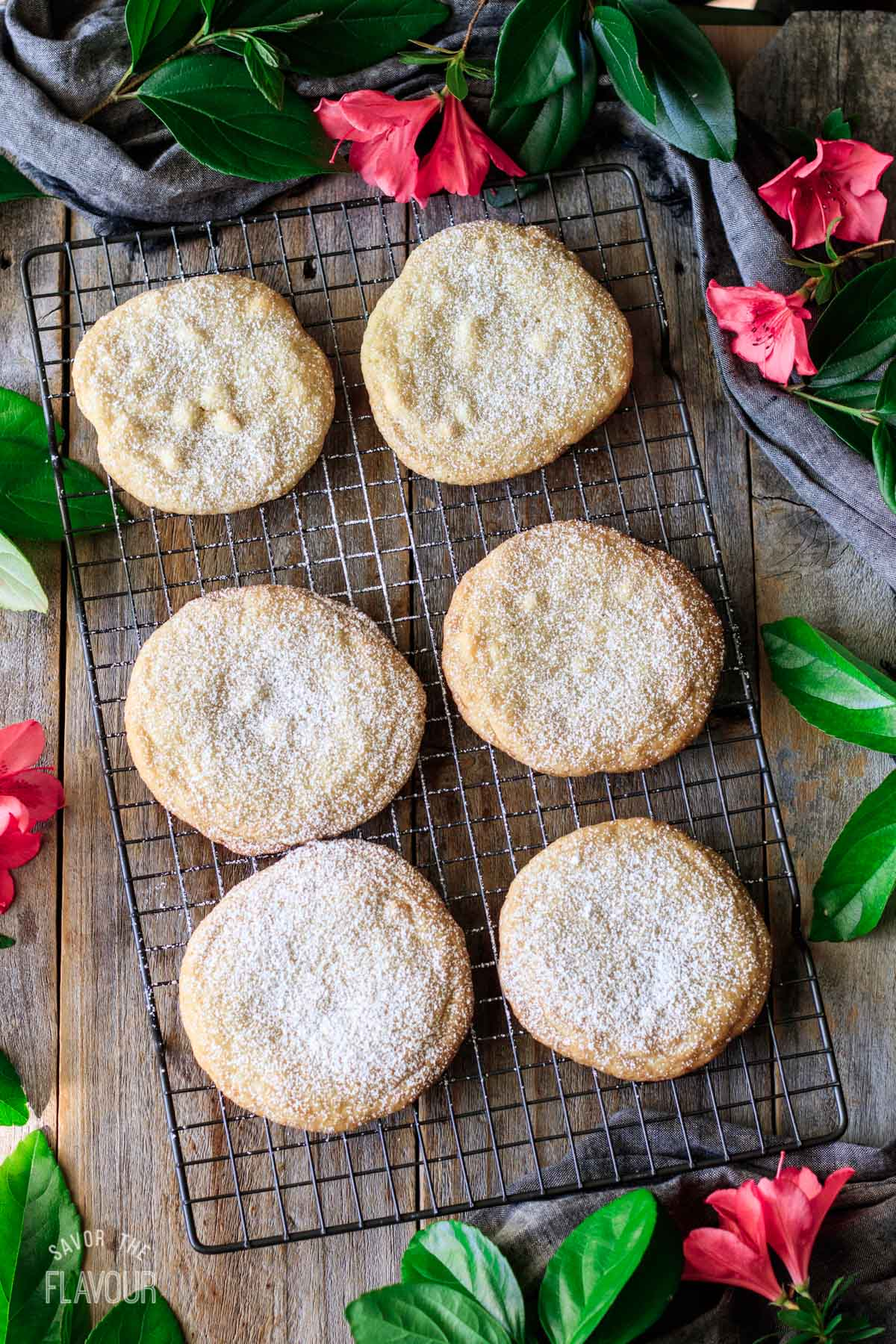 lemon drop cookies on a wire rack dusted with powdered sugar