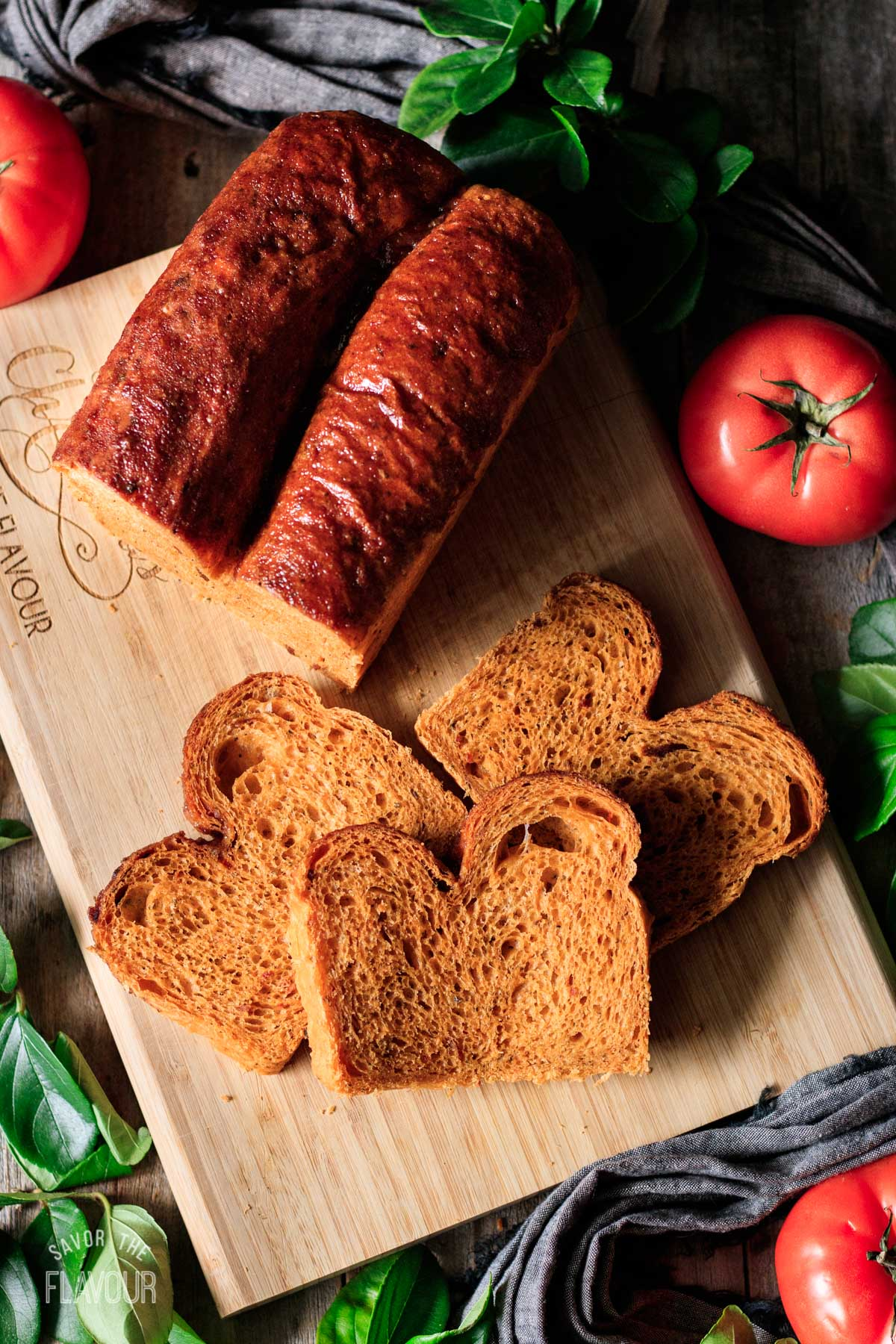slices of tomato basil bread on a cutting board with the loaf