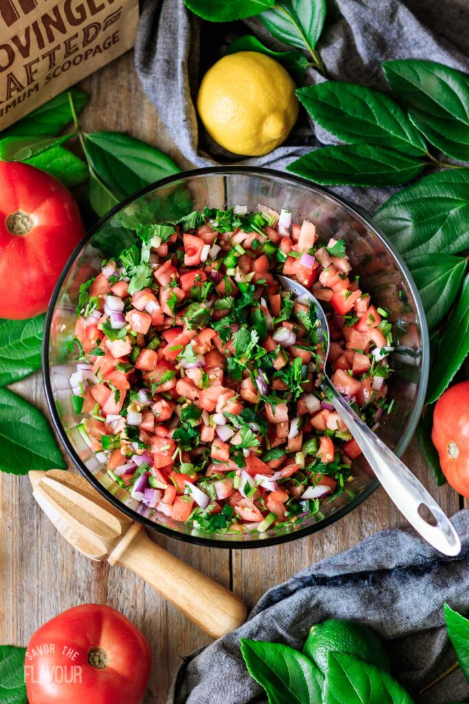 chopped tomato, onion, jalapeño, and cilantro in a glass bowl